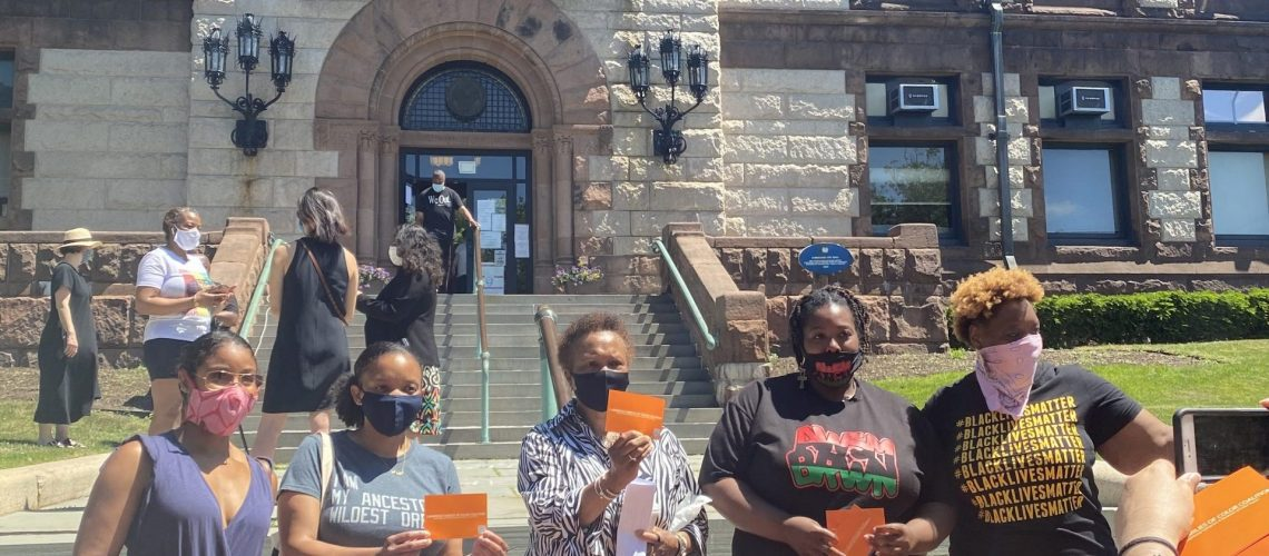 [image description: Five people wearing masks holdu up orange postcards and stand in front of a building